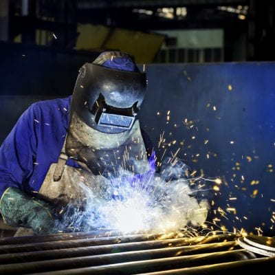 Worker dressed in protective uniform welding metal frame